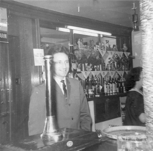 Lonnie behind a  bar.